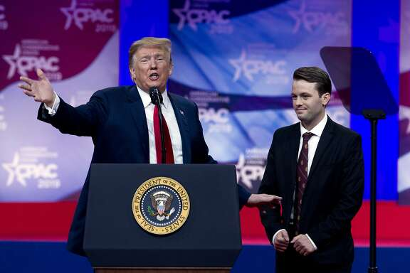 In this March 2, 2019 photo, President Donald Trump invites to the podium, Hayden Williams, a field representative of the Leadership Institute, who was assaulted at Berkeley campus, at the Conservative Political Action Conference, CPAC 2019, in Oxon Hill, Md. Trump is expected to order U.S. colleges to protect free speech on their campuses or risk losing federal funding. White House officials say Trump will sign an executive order Thursday requiring colleges to certify that their policies support free speech as a condition of receiving federal research grants. Trump initially proposed the idea during a March 2 speech to conservative activists.  (AP Photo/Jose Luis Magana)