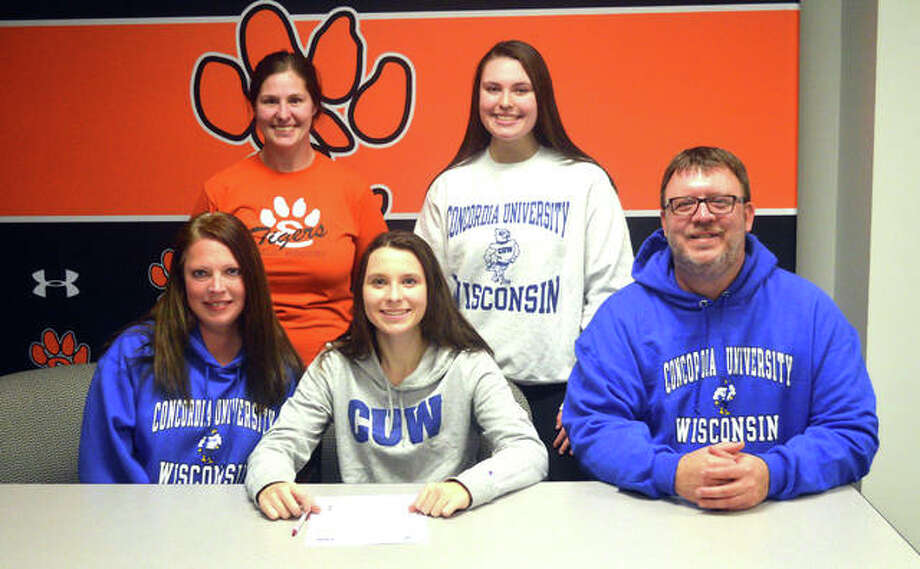 Edwardsville senior Alex Klamm, seated middle, is joined by her family and EHS coach Jaimee Phegley as she signs a letter of intent to play field hockey at Concordia University Wisconsin. Photo: Scott Marion/Intelligencer
