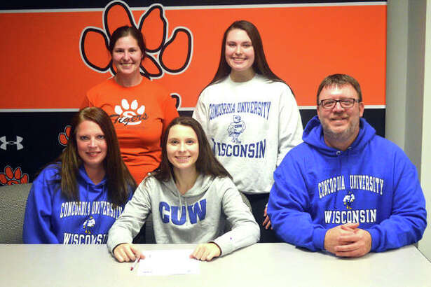 Edwardsville senior Alex Klamm, seated middle, is joined by her family and EHS coach Jaimee Phegley as she signs a letter of intent to play field hockey at Concordia University Wisconsin.