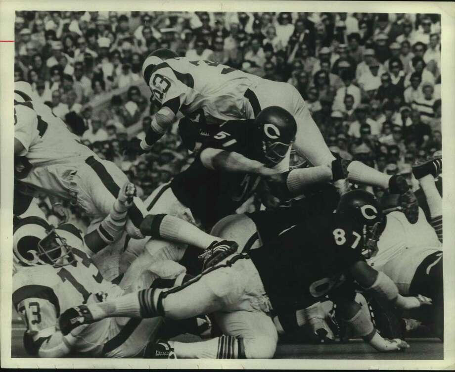 Dick Butkus of the Chicago Bears upends Los Angeles Rams' running back Willie Ellison in an NFL game. Ellison, a former Pearland substitute teacher, died March 11 and his funeral was held today at Brentwood Baptist Church. / Houston Chronicle