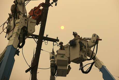 FILE - In this Nov. 9, 2018 file photo, Pacific Gas & Electric crews work to restore power lines in Paradise, Calif. PG&E says it won't award $130 million in employee bonuses because of its recent bankruptcy filing. The San Francisco Chronicle reported Saturday, Feb. 23, 2019 that interim chief executive John Simon cited California's deadly wildfires and the company's precarious financial state in an internal email message to workers on Friday. (AP Photo/Rich Pedroncelli, File)