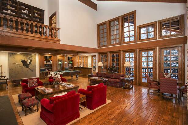Hardwood flooring and a beamed ceiling finish a grand living room at 723 Fairway Road in Sun Valley, Idaho.