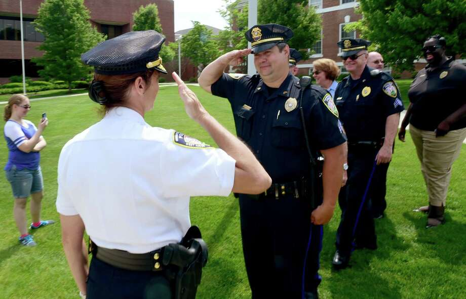 New University of New Haven Police Chief Tracy L. Mooney, left, returns a salute from UNH police Sgt. Kevin Holster after a swearing in ceremony for Chief Mooney Wednesday, June 1, 2016 at the University of New Haven. Mooney, a former Milford Police deputy police chief and the first female police chief at the university, replaces retired UNH police chief Mark DeLieto. Photo: Peter Hvizdak / Hearst Connecticut Media / ©2016 Peter Hvizdak