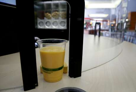 A completed order is automatically pushed towards a portal by a Blendid robotic smoothie-making kiosk during a test run at the Market Cafe on the USF campus in San Francisco, Calif. on Friday, March 22, 2019. The automated smoothie machine goes fully operational on Monday.
