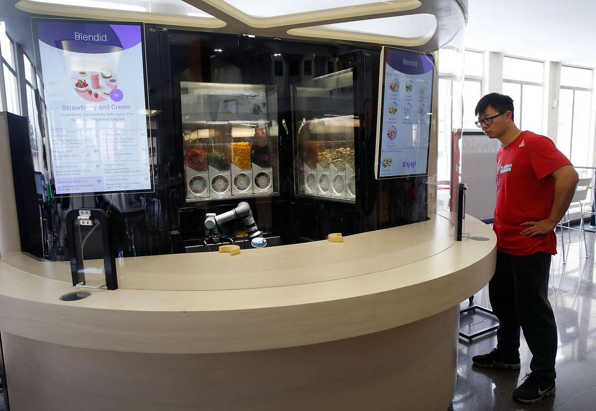 Norman Yu, a robotics engineer with Blendid, puts the autonomous smoothie-making kiosk through its paces during a test run at the Market Cafe on the USF campus in San Francisco, Calif. on Friday, March 22, 2019. The automated smoothie machine goes fully operational on Monday.