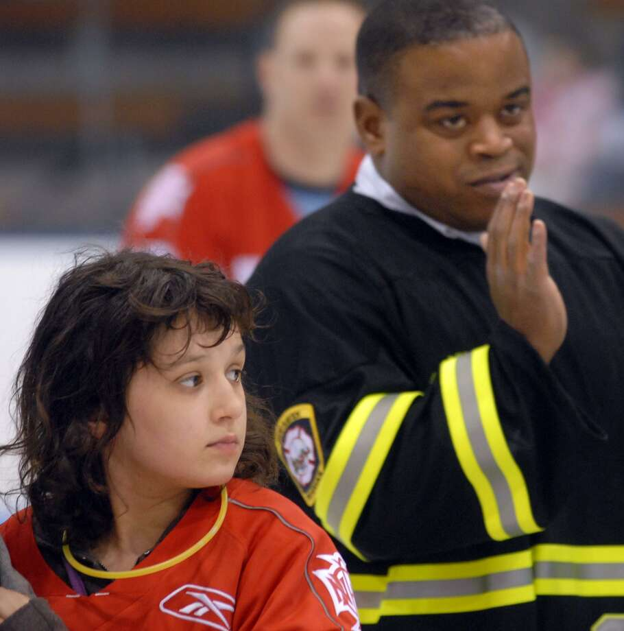 NE3/29/08 2PDFD ML0444G The 12th Annual Chief's Cup Benefit Hockey Game was played at Ingalls Rink, Yale Univ. between the New Haven Fire Dept. and Police Dept. Proceeds benefited four people including Kaycie Begley age 10 of Milford left with Assistant Fire Chief Ralph Black in the background. Photo by Mara Lavitt