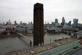 The chimney of the Tate Modern is pictured in front of the River Thames and the City of London skyline from the top of the extension of the Tate Modern in London, England. The Tate group has announced that will no longer accept contributions from the Sackler family, which owns Purdue Pharma.