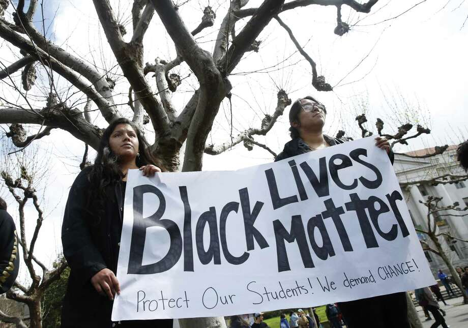 Cal students Yessenia Hernandez-Cruz (left) and Glendy Ramon hold a banner on Sproul Plaza at UC Berkeley on Wednesday, March 20, 2019 where hundreds gathered for a noontime rally to protest what the demonstrators are calling a racial profiling incident by the university's police department on March 8. Photo: Paul Chinn / The Chronicle / ONLINE_YES