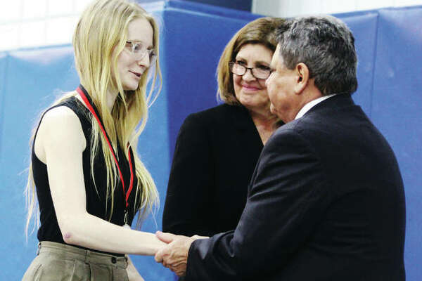 Alton High School senior Hannah Camerer is congratulated by Alton School Superintendent Mark Cappel at the 31st Annual Silver Medallion Academic Excellence Awards Banquet, held Thursday at Lewis and Clark Community College. The event honors students in the top 8 percent at 22 local high schools. Also recognized are a teacher of the year, retiring superintendents, and male and female scholar athletes of the year.