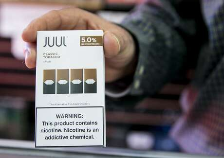 Walid Rahman holds a Juul cartridge container while working behind the counter at The Town Smoke Shop in the Mission district of San Francisco, Calif. Thursday, March 21, 2019.