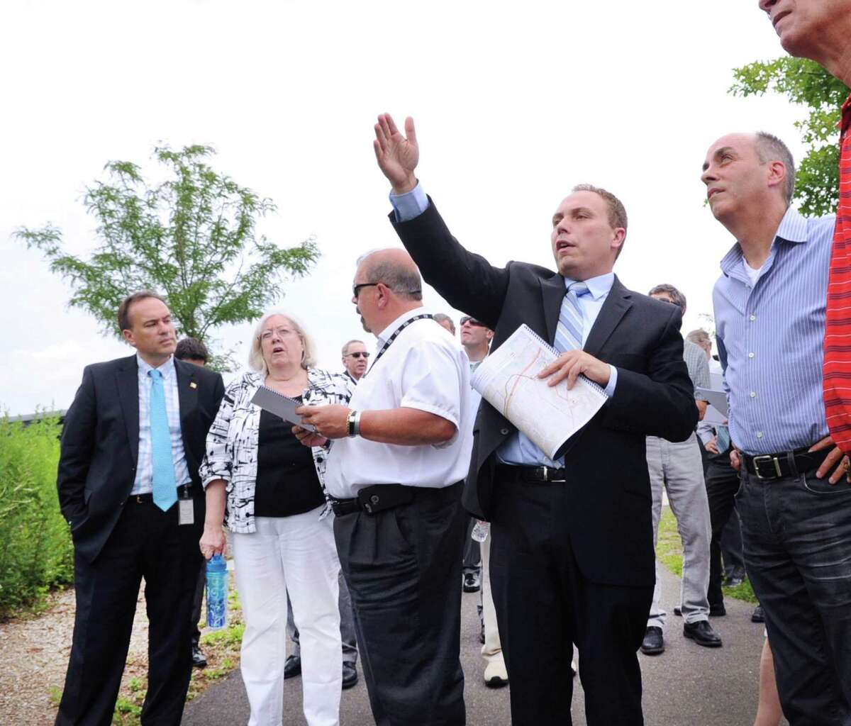 Second from right, Jason Cabral of the firm Burns & McDonnell, an engineering, architecture, and construction firm, leads the Connecticut Siting Council tour of Cos Cob Park in Greenwich July 13, 2017. At left is Greenwich First Selectman Peter Tesei.