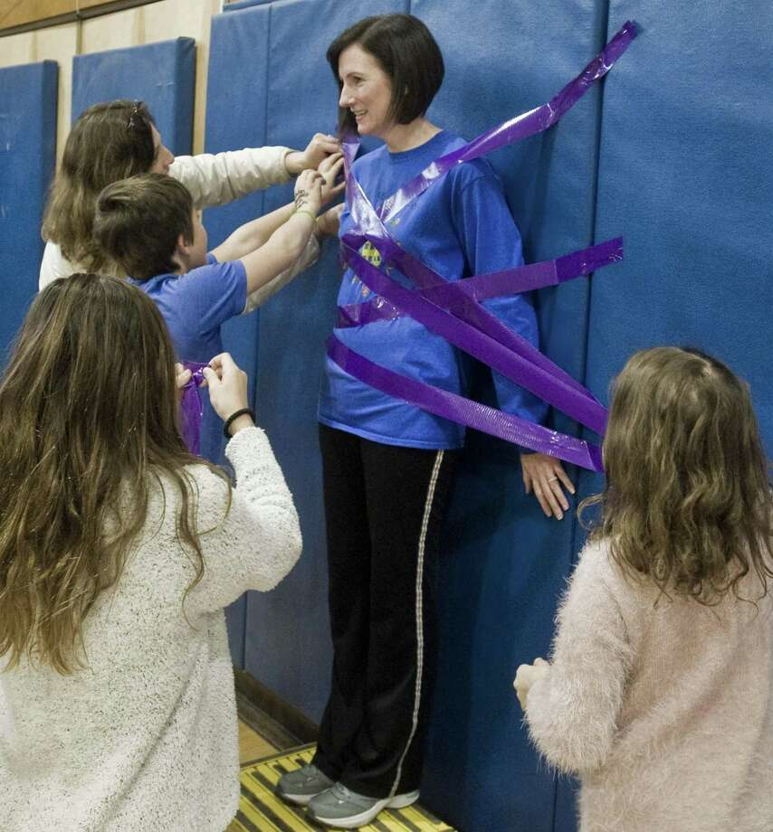 North Street School Principal, Jill Flood, begins to be taped to the gym wall as each piece of tape is purchased for the Pennies for Patients fundraising campaign to benefit the Leukemia and Lymphoma Society. Friday, March 22, 2019 Photo: Scott Mullin / For Hearst Connecticut Media / The News-Times Freelance