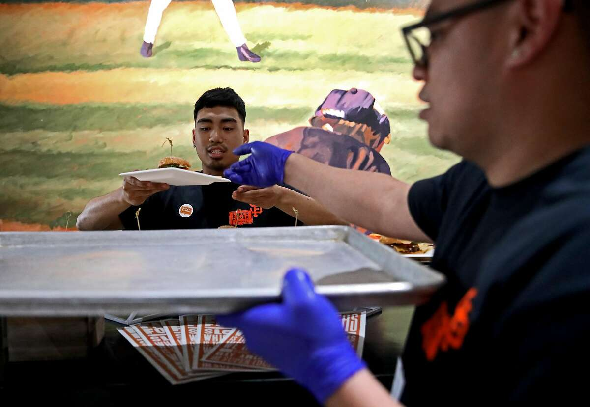 Matthew Palma (left) and Edwin Mendoza, employees with Super Duper Burgers, add more burgers to their booth for sampling during the San Francisco Giants Media Day at Oracle Park in San Francisco, Calif., on Friday, March 22, 2019.