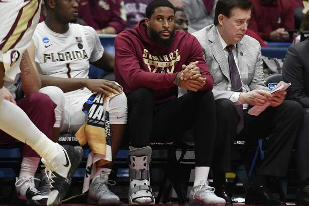 Florida State's Phil Cofer (0) sits on the bench with a boot on his right foot during the Seminoles win over Vermont in the NCAA tournament on Thursday in Hartford. Cofer learned after the game that his father Mike, a former NFL linebacker, passed away following a long illness.