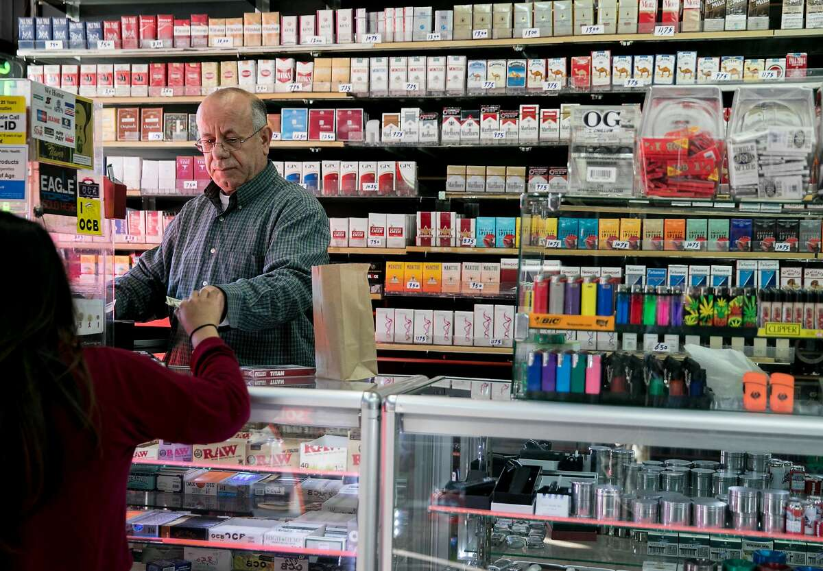 Walid Rahman works behind the counter of The Town Smoke Shop in the Mission district of San Francisco, Calif. Thursday, March 21, 2019.