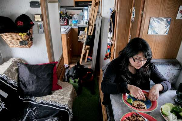 Yesica Prado enjoys tacos while sitting inside her RV parked near Gilman Street in Berkeley, Calif. Tuesday, March 19, 2019.