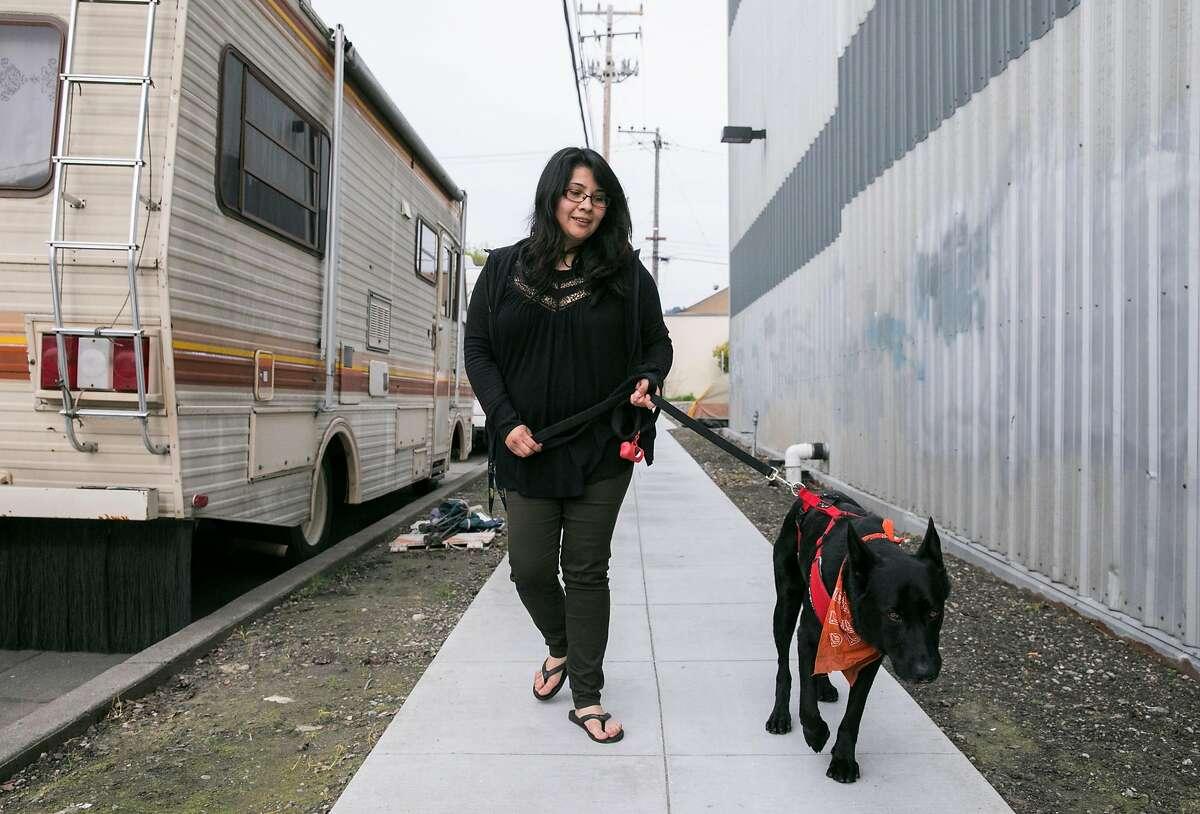 Yesica Prado walks her dog Kodak past a row of RVs parked near Gilman Street in Berkeley, Calif. Tuesday, March 19, 2019.