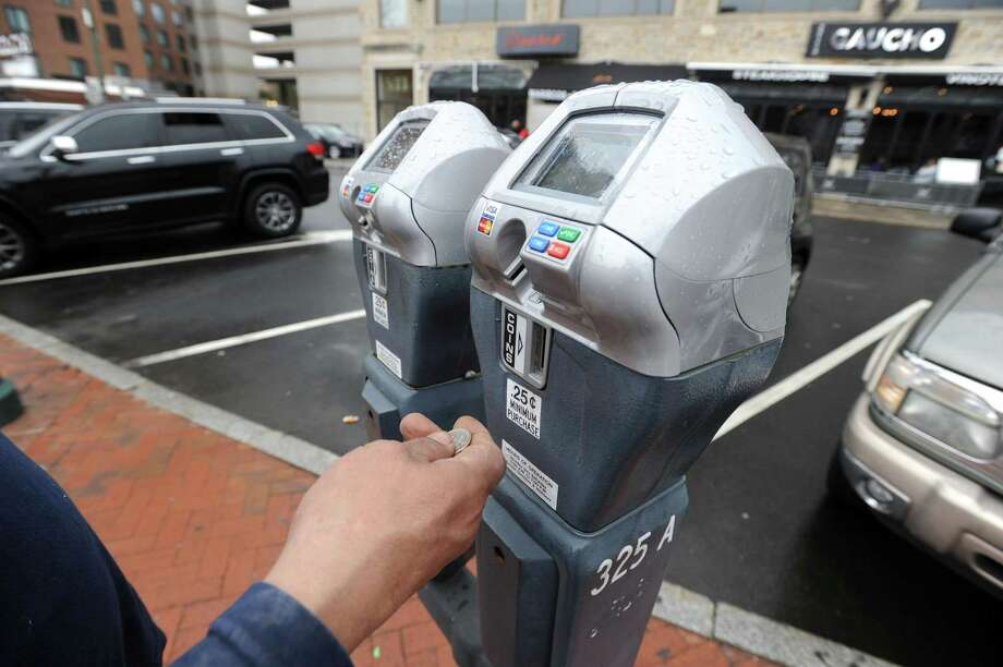 A customer is photograph on Thursday, March 21, 2019 paying for parking on West Park Place in Stamford, Connecticut. The city plans to increase fees to park at city meters, garages and lots downtown, which downtown merchants and powerbrokers don't want. Photo: Matthew Brown / Hearst Connecticut Media / Stamford Advocate