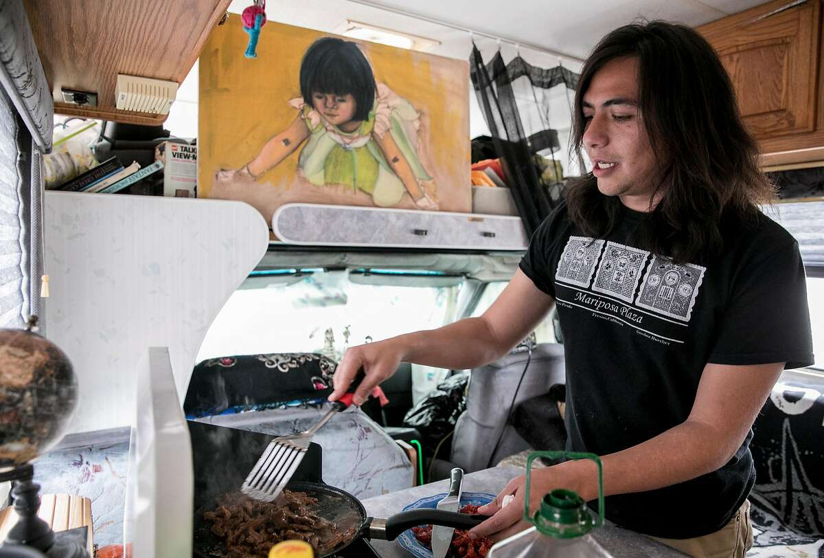 Christian Torres works to cook dinner on a camping stove while in the RV he shares with Yesica Prado parked near Gilman Street in Berkeley, Calif. Tuesday, March 19, 2019.