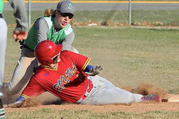 Carrollton first baseman Hunter Flowers (back) keeps the tag on Roxana's Weston Renaud, who is called safe to avoid getting doubled off first on a flyball to center field on Friday at Roxana Park.
