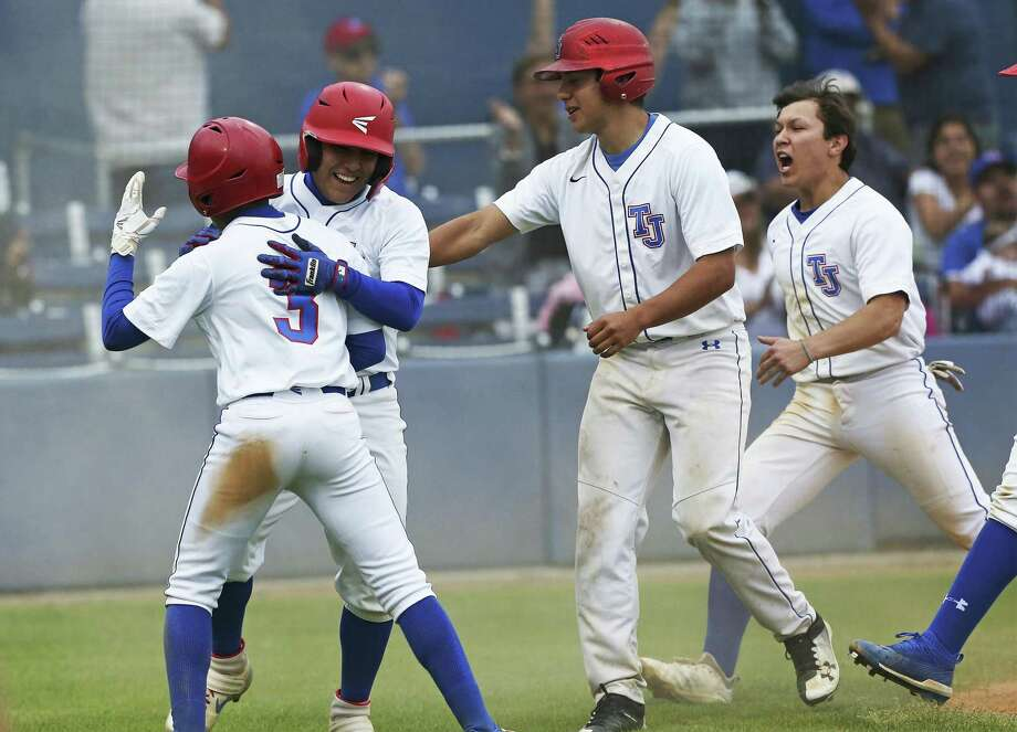 Jason Romo celebrates with his teammates after scoring to win the game in the bottom of the seventh on a pass ball at home plate as Jefferson beats Highlands 5-4 in high school baseball at the SAISD Sports Complex on March 22, 2019. Photo: Tom Reel, Staff / Staff Photographer / 2019 SAN ANTONIO EXPRESS-NEWS