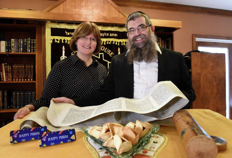 Rabbi Mendel Rubin and his wife, Raizy, are pictured with Purim items, that include; a Megillah scroll, gragger noisemakers and hamantaschen pastries on Friday, March 22, 2019, at Shabbos House in Albany, N.Y. Shabbos House is a Jewish support center for students at the University at Albany. (Will Waldron/Times Union)