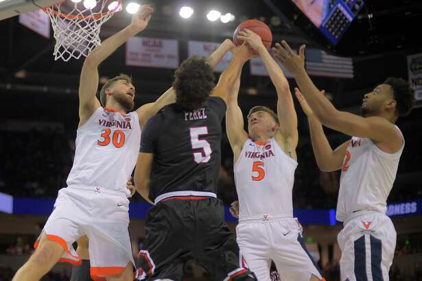 Virginia's Kyle Guy (5) grabs a rebound in a crowd of Jay Huff, left, De'Andre Hunter, right, and Gardner Webb's Jose Perez.