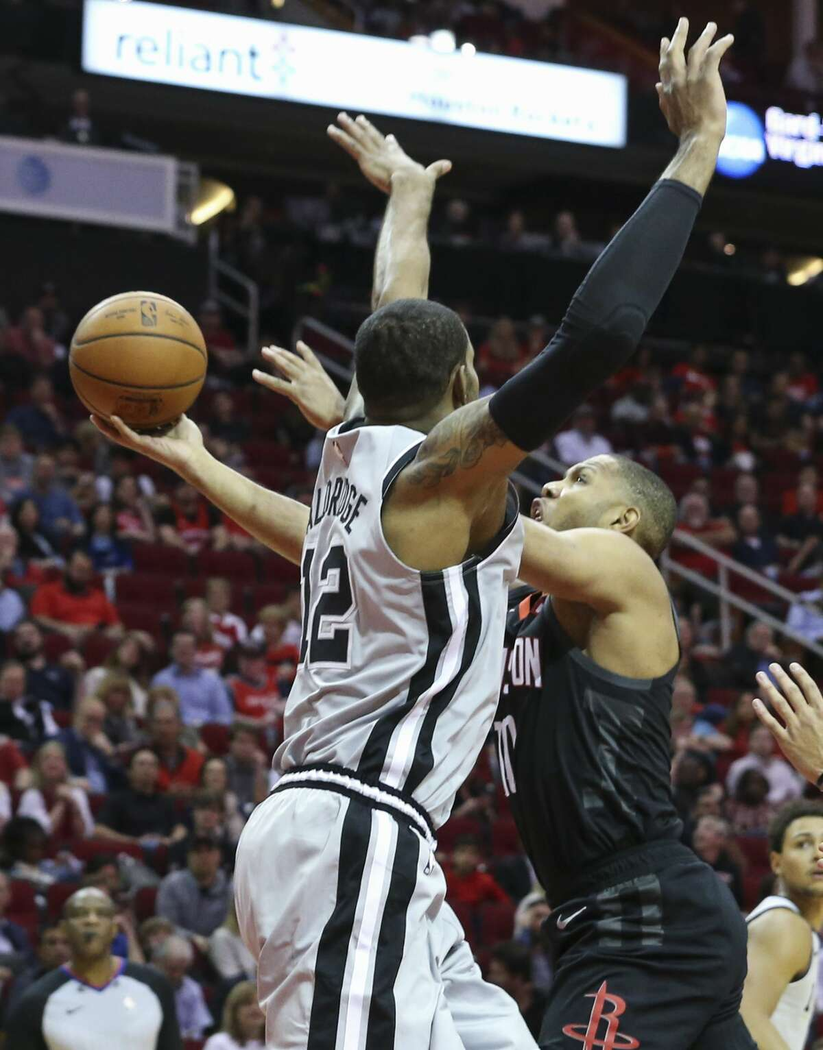 Houston Rockets guard Eric Gordon (10) is fouled by San Antonio Spurs center LaMarcus Aldridge (12) while going for the basket during the second quarter of the NBA game at Toyota Center on Friday, March 22, 2019, in Houston.