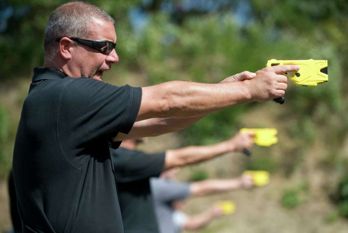 FILE- In this Sept. 25, 2012 file photo, Cherry Hill Township Police Officer Patrick Higgins takes part in a taser training session at the Gloucester Township, N.J., Police Training Facility. On Friday, March 22, 2019 a federal judge has ruled that New York's ban on personal ownership of stun guns is unconstitutional. Friday's ruling by a district judge in Utica, N.Y., is the latest in a series of court decisions that have led to the loosening of restrictions on the weapons in several states. (AP Photo/Camden Courier-Post via AP, File)