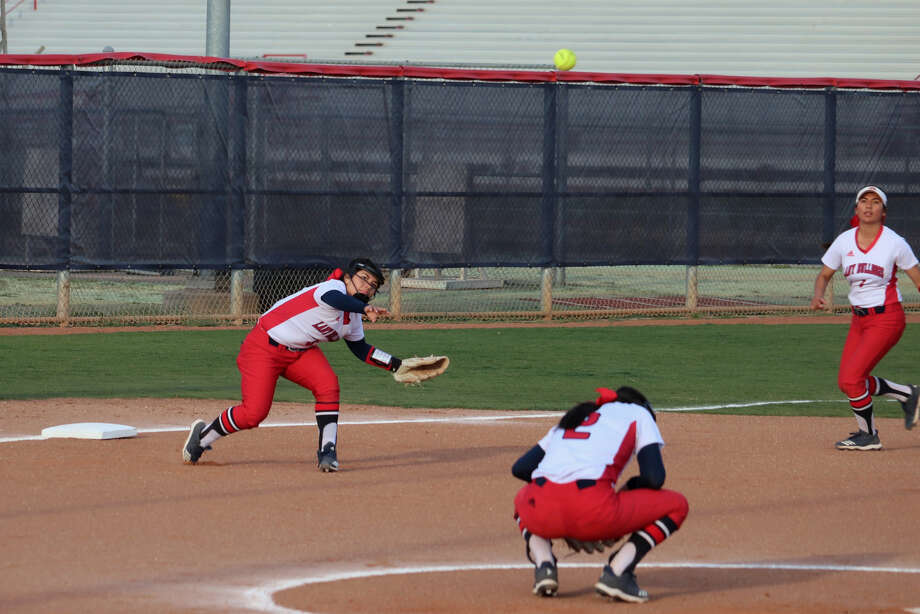 Plainview Lady Bulldogs third baseman Lauren Alderete (left) fires a throw to first base for the out as pitcher Esme Lucio (2) ducks down and shortstop Jenna Sepeda (right) looks on during a District 3-5A softball game against Lubbock High on Friday in Plainview. Photo: Courtesy Of Curtis Bailey