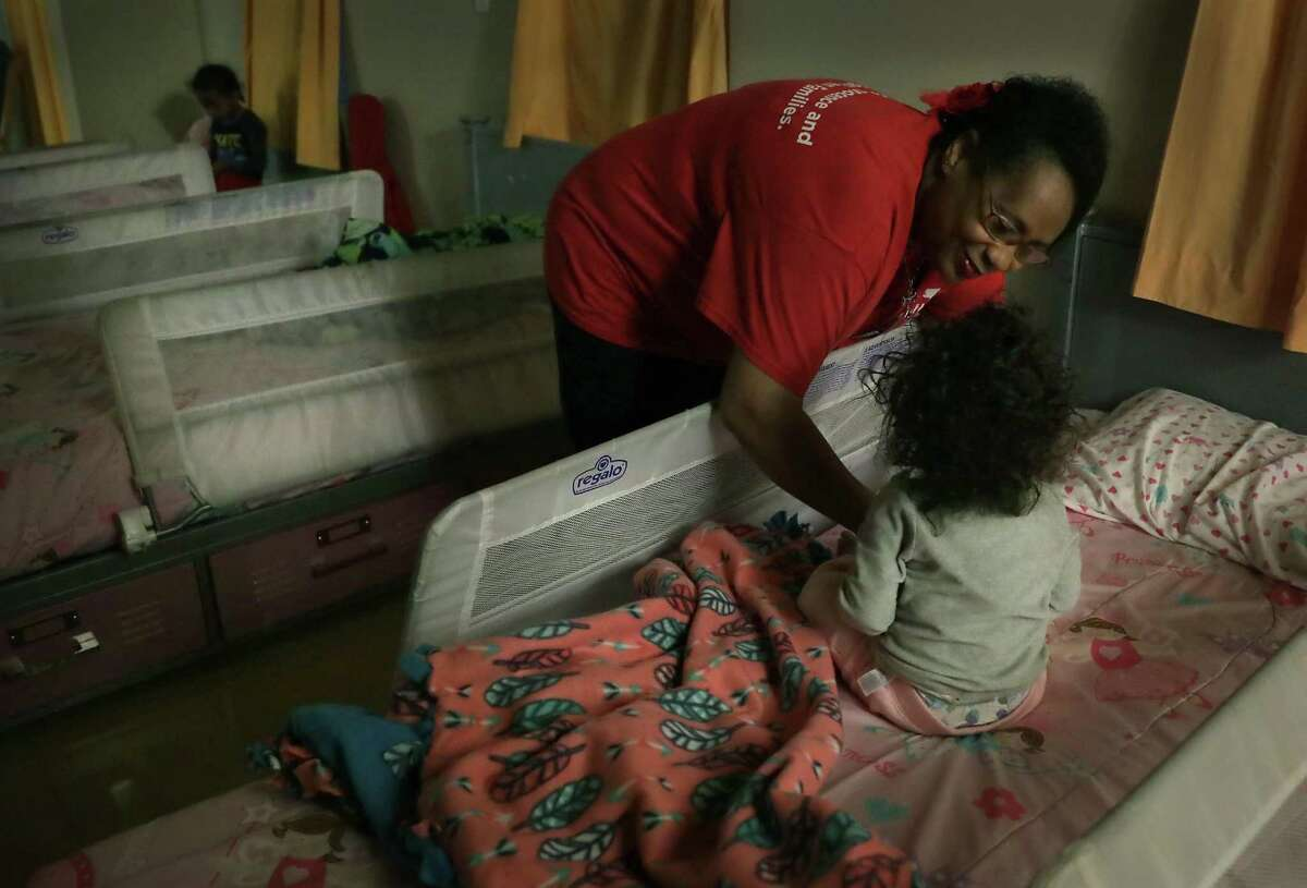 """Shirley Harris, known as """"Mama Shirley"""" to the children at The Children's Shelter, helps a little girl wake up. She has cared for many abused children over the past 28 years working at the shelter, on Friday, March 1, 2019."""