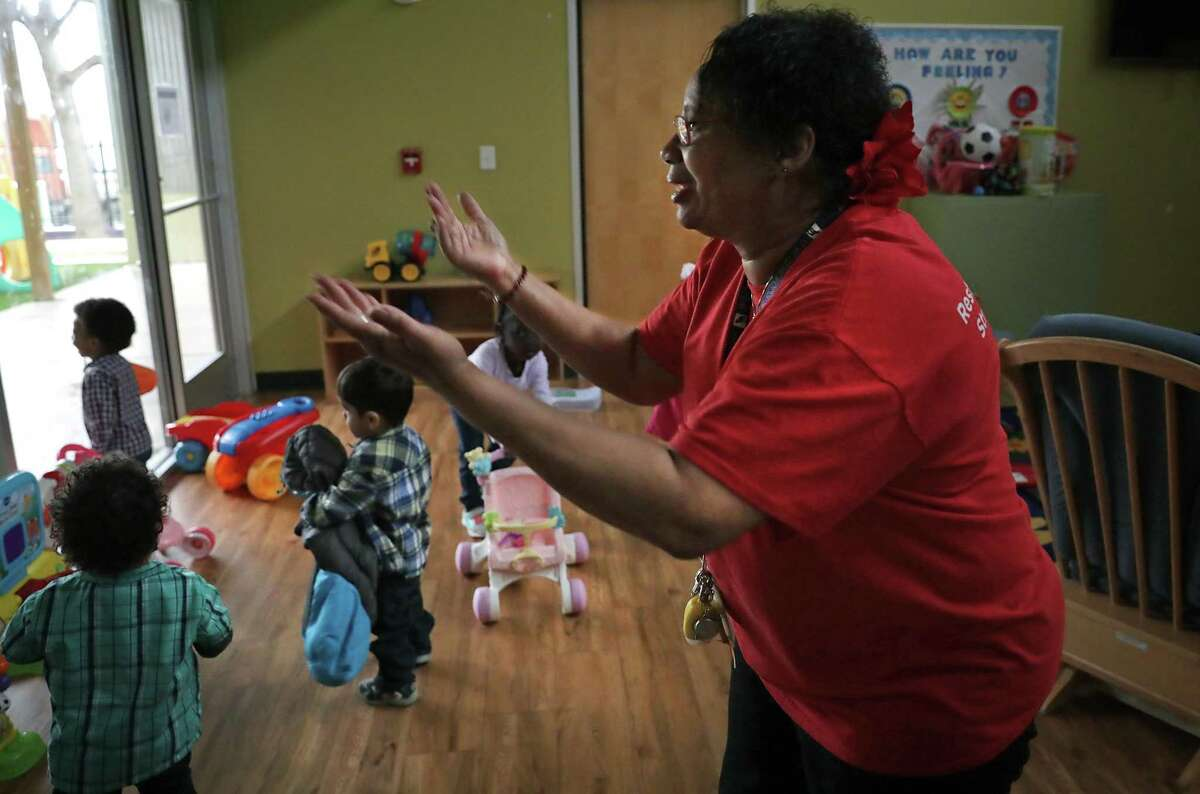 """Shirley Harris, known as """"Mama Shirley"""" to the children at The Children's Shelter, motions to another age group she works with through a window."""
