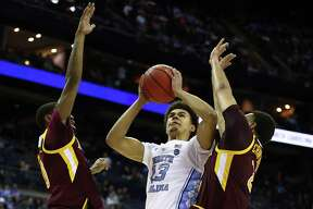 COLUMBUS, OHIO - MARCH 22: Cameron Johnson #13 of the North Carolina Tar Heels shoots against E.J. Crawford #2 and Rickey McGill #0 of the Iona Gaels during the second half of the game in the first round of the 2019 NCAA Men's Basketball Tournament at Nationwide Arena on March 22, 2019 in Columbus, Ohio. (Photo by Gregory Shamus/Getty Images)
