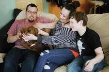From left, Robert Allison, Rosetta Allison and NathanJay Allison, 11, cuddle with their new dog, named Blue, inside their home, on Wednesday in Harrison. (Katy Kildee/kkildee@mdn.net)
