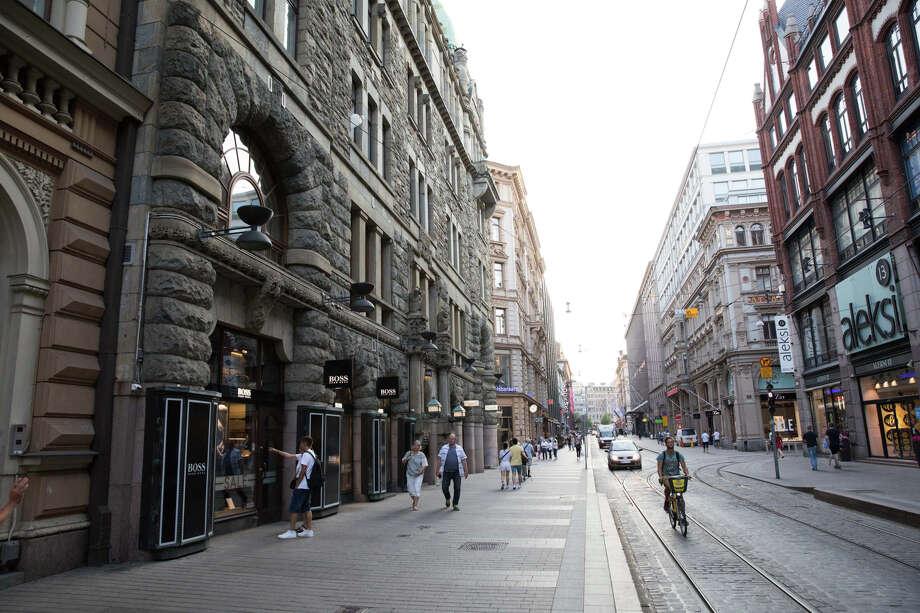 Pedestrians pass retail outlets along Aleksanterinkatu street in Helsinki, Finland, on July 16, 2018. Photo: Bloomberg Photo By Chris Ratcliffe. / © 2018 Bloomberg Finance LP