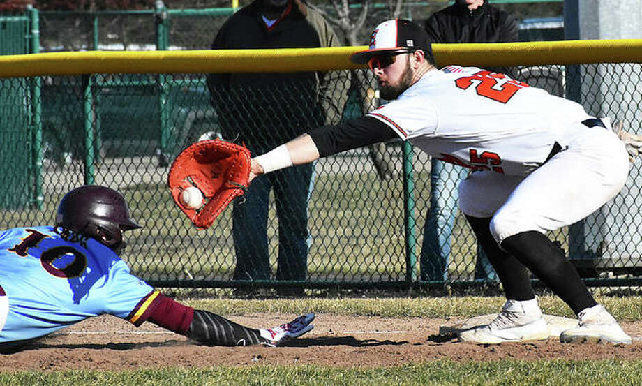 A De Smet baserunner dives back to the bag while Edwardsville first baseman Max Ringering takes the pickoff throw Friday at Tom Pile Field in Edwardsville. Photo: Matt Kamp / Hearst Illinois