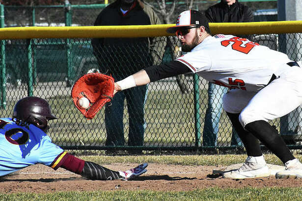 A De Smet baserunner dives back to the bag while Edwardsville first baseman Max Ringering takes the pickoff throw Friday at Tom Pile Field in Edwardsville.
