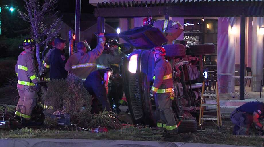 Emergency personnel from multiple law enforcement agencies and the San Antonio Fire Department work to free men from the wreckage of a pickup truck after police say the men crashed following a high-speed chase through Bexar County and San Antonio Saturday morning, March 23, 2019. Photo: 21 Pro Video