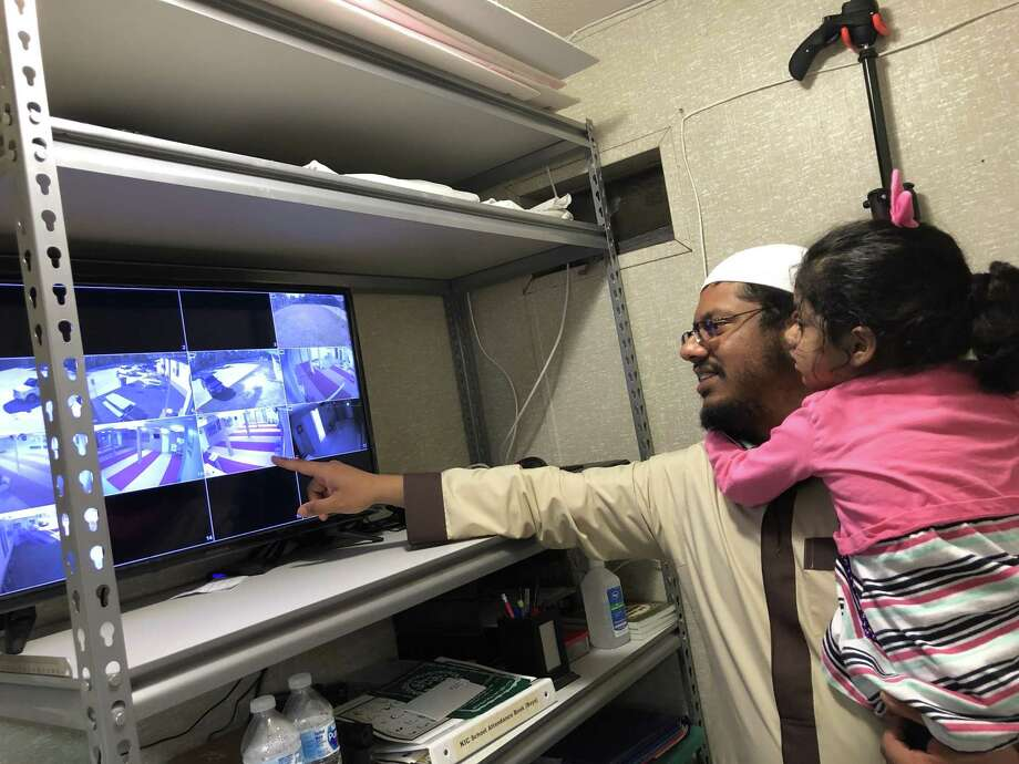 Kingwood Islamic Center Imam Ahmad Siddiqi and his daughter Zainab observe movements on the mosque's security camera system. Photo: Nguyen Le / Staff Photo