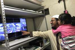 Kingwood Islamic Center Imam Ahmad Siddiqi and his daughter Zainab observe movements on the mosque's security camera system.