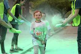 Runners are sprayed with color during the Katy Color Run in Katy on Saturday, March 23, 2019.