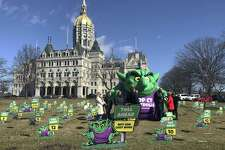 """Opponents of highway tolls in Connecticut pose in front of an inflatable """"Toll Troll"""", Tuesday, March 19, 2019, outside the Connecticut State Capitol in Hartford, Conn. The conservative Yankee Institute for Public Policy organized the protest ahead of a planned committee vote on tolls."""
