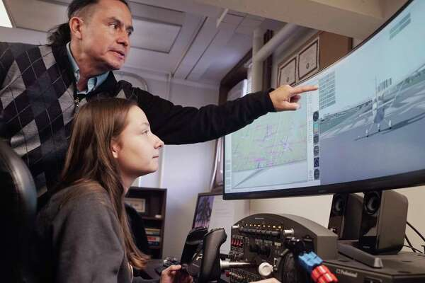 Carlos Varela, left, an associate professor of computer science at RPI, works with computer science freshman student, Marie Petitjean, as she operates a flight simulator at RPI on Monday, March 18, 2019, in Troy, N.Y. The simulator is used to generate data that is used to validate the model used in their research. (Paul Buckowski/Times Union)
