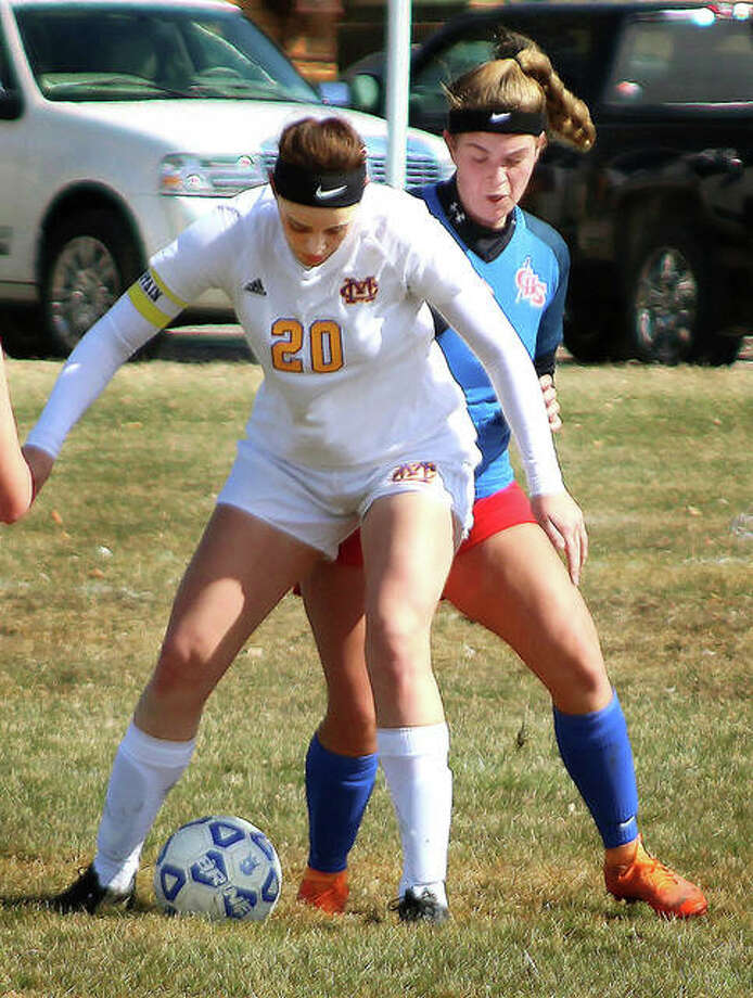 Civic Memorial's Anna Hall (20) shields the ball from Carlinville's Isabelle Stoops during action Saturday in the Carlinville Girls Spring Cup tournament at Blackburn College in Carlinville. Hall scored all three of her team's goals in a 3-0 victory. Photo: Pete Hayes | The Telegraph