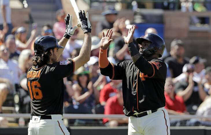 San Francisco Giants' Pablo Sandoval, right, shares congratulations with Aramis Garcia after both scored against the Arizona Diamondbacks in the fourth inning of a spring training baseball game Saturday, March 23, 2019, in Scottsdale, Ariz. (AP Photo/Elaine Thompson)