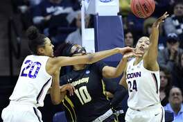 UConn's Olivia Nelson-Ododa (20) and Napheesa Collier defend against Towson's Janeen Camp during a NCAA tournament first-round game Friday in Storrs.