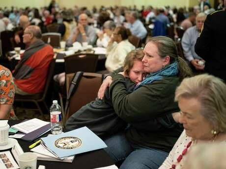 Samantha Oliver, center, hugs her mother Gillien Oliver, second right, after talking about their relative, Pvt Erford M. Johnson who served in the Army during WWII, during an event hosted by the United States' Defense POW/MIA Accounting Agency where military families were given information about their missing military relatives in San Antonio on Saturday, March 23, 2019. Samantha Oliver credited her relative as her inspiration for wanting to join the military once she finishes college. Gillien Oliver also served in the military.