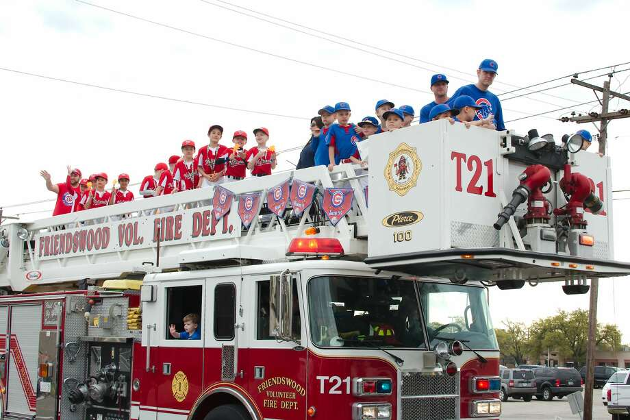 Members of the Friendswood Nationals and Cubs youth league baseball teams waves to the crowd during the youth sports parade Saturday, Mar. 23. Photo: Kirk Sides/Staff Photographer