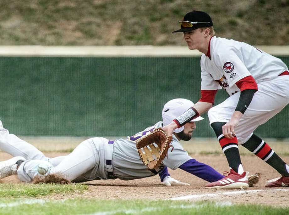 Civic Memorial's Gavin Lyday (15) dives back into first base just under the tag of Alton High first baseman Riley Phillips (11) Saturday during the Redbirds' see-saw 11-10 eight-inning victory over the Eagles at AHS. Michael Reeder led Alton batters with three hits with two RBIs. Four other Redbirds had a pair of hits. Photo: Nathan Woodside | The Telegraph
