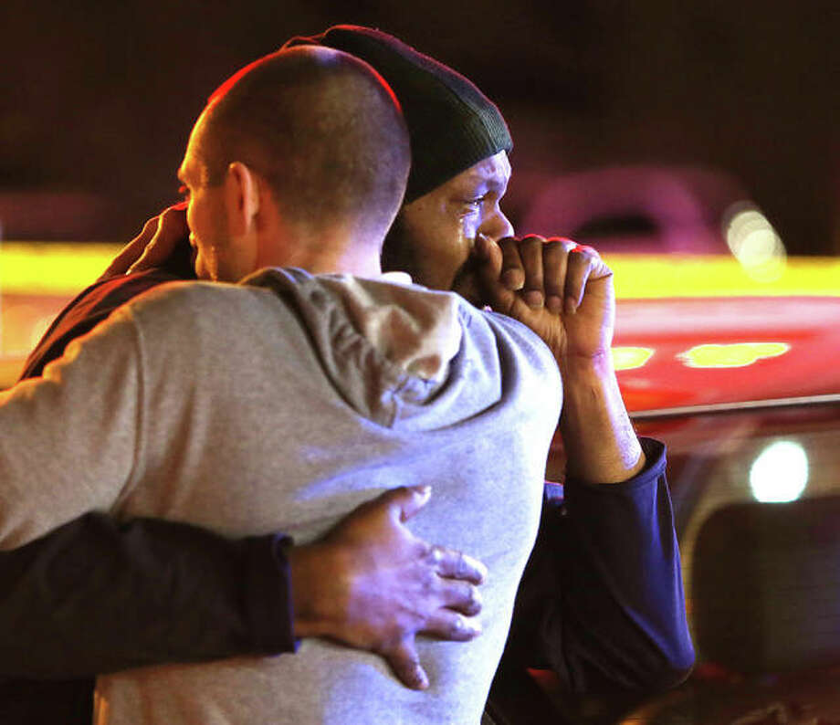 "Alton Police Chief of Detectives Lt. Jarrett Ford, left, consoles a family member late Friday night at the scene of a fatal shooting inside the Alton Shell station at the corner of Brown Street and Washington Avenue. A man was shot and killed just inside the south entrance to the station shortly after 7 p.m. following what witnesses have described as an ""argument"" between the two people. The apparent suspect was apprehended a short time later by Illinois State Police after they were involved in a car crash on Illinois Route 140 at Route 159 east of Meadowbrook. An employee inside the store said he narrowly escaped being shot as he tried to separate the two people involved in the altercation. Photo: John Badman 